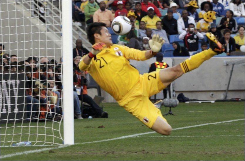 DER ER BALLEN! Japan-målvakt Eiji Kawashima snur seg i luften og ser at ballen vil gå i mål til 1-0 for Nederland. Foto: Reuters