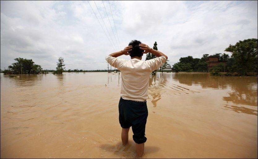 FORTVILER: Et av flomofrene i det sørlige Kina fortviler over flomvannet som har drept over 100 menneskeri Kina. Foto: Reuters