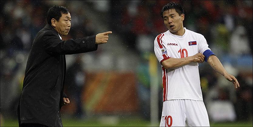 SELVKRITISK: Kim Jong-Hun mente han burde gjort mye annerledes mot Portugal, og at spillerne ikke kunne lastes for tapet. Her snakker han med Hon Yong-Ho underveis i kampen. Foto: AP