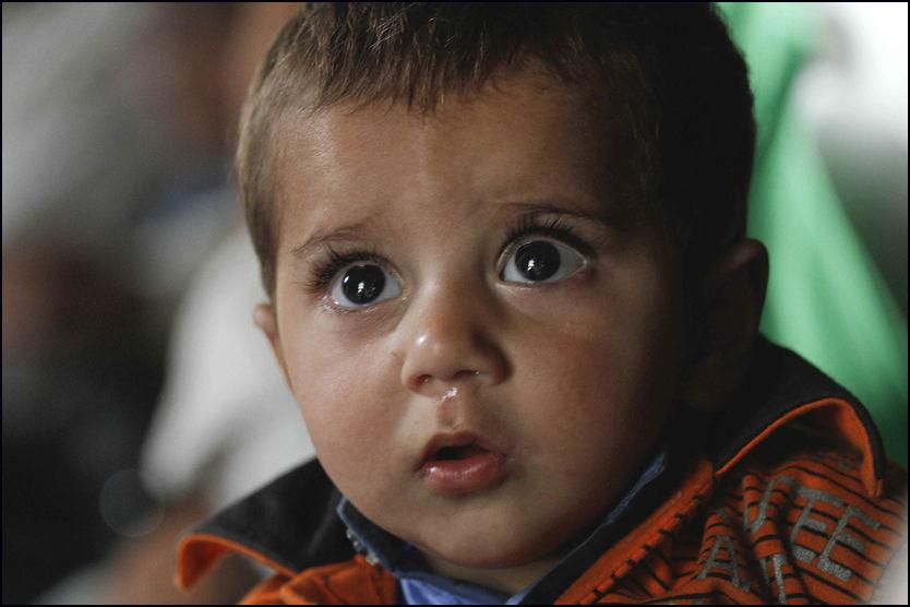 HVOR ER DU?: Pjokken med de store øynene venter på faren etter at familien tirsdag ble reddet fra Kalam i Swat-dalen, en av de hardest rammede områdene i Pakistan. Foto: AP