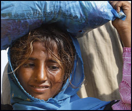 BÆRER TUNGT: En ung jente har eiendelene sine på hodet mens hun forsøker å flykte fra de verste flomorådene i Muzaffargarh nær Multan. Foto: AP