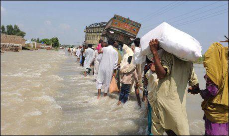 PÅ FLYKT: Flomofre forlater noen av de hardest rammede områdene. Foto: AFP