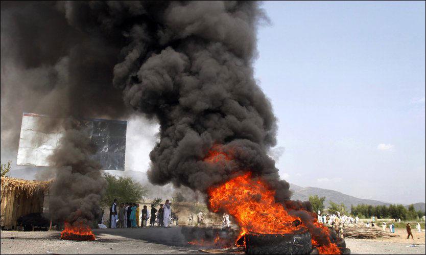 FLAMMER: Demonstranter i Jalalabad satte fyr på bildekk. Foto: AP