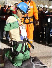 TAKKNEMLIG: Carlos Mamani kneler etter å ha kommet ut av kapselen. FOTO: AFP.