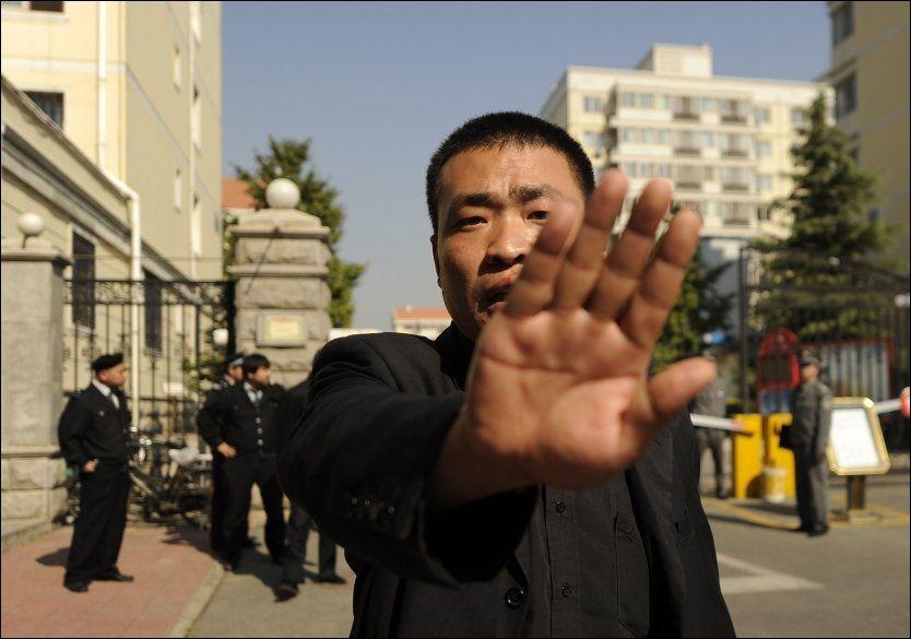 KRITISKE: En kinesisk politimann forsøker å stoppe fotografer i å ta bilde av huset til fredsprisvinnende Liu Xiaobo. Foto: AFP