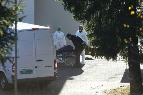 FUNNET DØD: Kvinnens kropp blir her fraktet bort. Foto: Scanpix