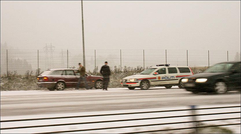 SOMMERDEKK-SNURR: Flere bilister kjører på sommerdekk vinteren gjennom. I overgangsfasen nå om dagen er det flere som ikke har fått lagt om, og tar sjansen. Her hjelper politiet til med å lede trafikken forbi en bil som har snurret med sommerdekk i nærheten av Olavsgård i Akershus. Bildet er fra en tidligere vinter. Foto: Scanpix