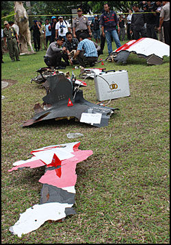 FLYDELER: Indonesisk politi plukker opp delene fra Airbussen. Foto: AFP