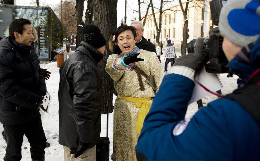 SINT: - Disse folkene er dårlige folk! De samarbeider med USA og lager bare problemer for Kina, ropte Ming Xin Dai (med ryggen til) oppskaket etter en av dem (mannen med kinesisk drakt) som viste sin støtte til fredsprisvinneren. Foto: ROGER NEUMANN