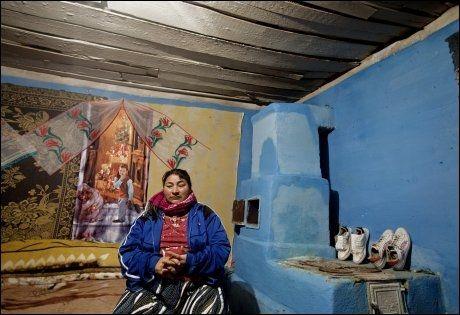 HJEMME IGJEN: Gulvet er hardstampet jord, veggene er pyntet med tøystykker og plakater. Husets eneste rom er på rundt ti kvadratmeter. Her bor fire mennesker. Akasiakrattet fungerer som toalett. I et badekar utenfor huset sildrer iskaldt vann kontinuerlig fra en slange. Iuliana tør ikke skru det av. Da kan det fryse. Foto: Annemor Larsen