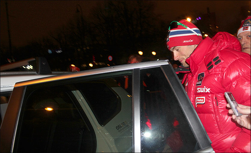 FORSVANT I ALL HAST: Petter Northug ble eskortert til en ventende bil bort fra premieseremonien mens hundrevis av mennesker fulgte med. Til h. medierådgiver Rolf Nereng. Foto: Øyvind Brenne