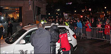 POPULÆR: Petter Northug ble fulgt av pressefotografene også etter at han hadde satt seg i den ventende bilen, mens hundrevis av tilskuere får med seg den i alle fall tilsynelatende dramatiske exiten. Foto: Øyvind Brenne
