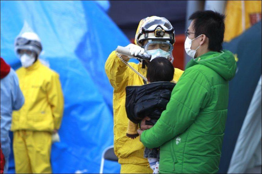 STRÅLING: Et barn som evakueres fra områdene rundt Fikushima-kraftverket undersøkes for radioaktiv stråling. Foto: Ap