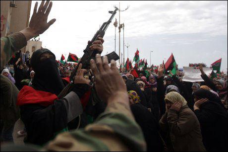 FEIRING: En kvinne skyter i luften med et maskingevær mens folkemassene i Benghazi feirer FN-resolusjonen. Foto: AFP