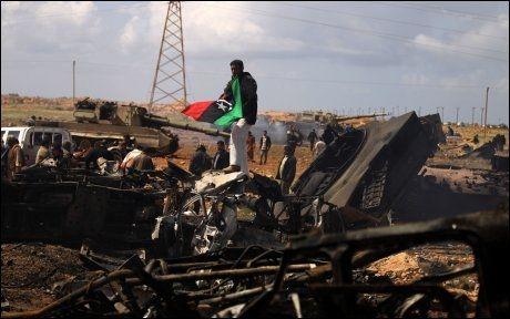 BOMBET: Opprørere feirer ved en ødelagt libysk stridsvogn vest for Benghazi. Foto: AFP