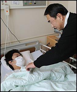 PÅ SYKEHUS: Pappa Akira Abe ser til sønnen Jin på sykehuset etter at han ble reddet. Han skal kun være lettere skadet etter å ha vært fanget ni dager i ruinene. Foto: AFP