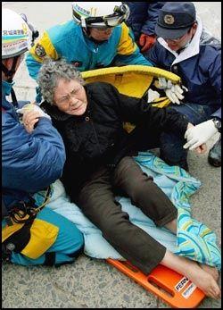 BESTEMOR: Sumi Abe (80) ble funnet på toppen av et sammenrast skap i det ødelagte huset. Her blir hun tatt hånd om av redningsmannskapene. Foto: AP Photo/Mainichi Shimbun, Takashi Morita
