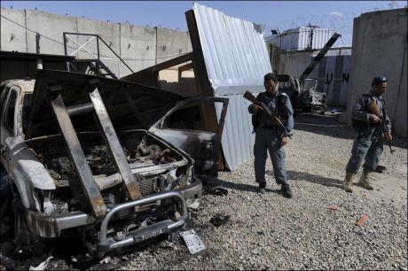 STÅR VAKT: Afghanske politimenn står vakt utenfor FN-bygget i Mazar-e Sharif etter angrepet fredag. Foto: AFP