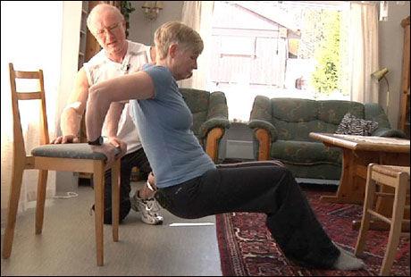 Gunnar Bråthen veileder Aud i hjemmeøvelsen dips på kjøkkenstol. Den gir styrke i overarmene. Foto: David Andresen