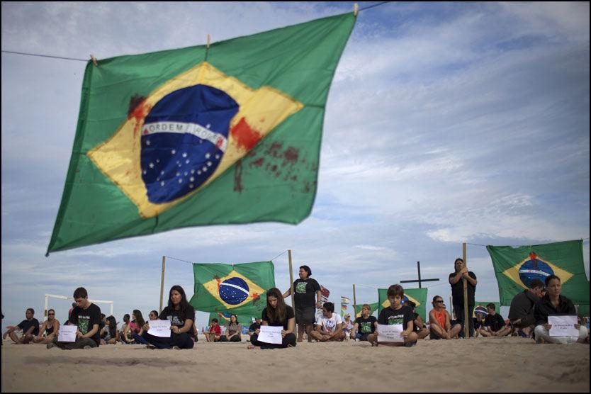 VIL SKJERPE LOVENE: Representanter fra bevegelsen for et tryggere Brasil samlet seg søndag på Copacabana for å minnes ofrene etter skoleskytingen forrige torsdag. Foto: AP
