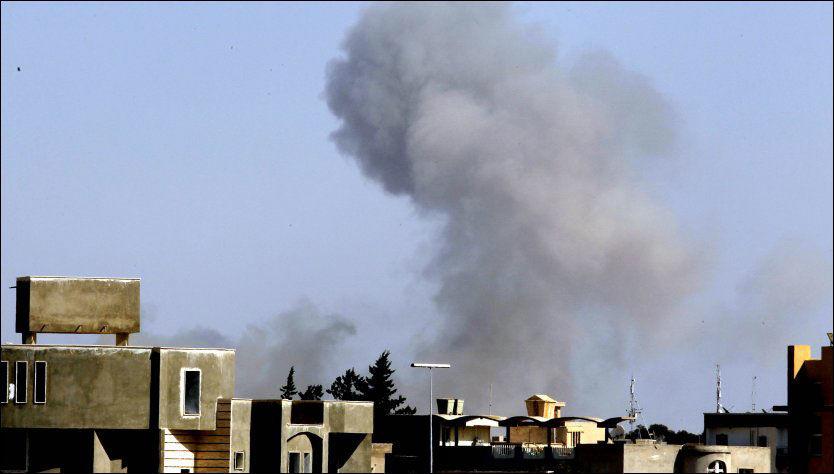 EKSPLOSJON: Røyk stiger opp fra bakken kort tid etter at eksplosjoner ble hørt i Tripoli. Foto: AP