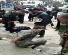FÅR BANK: Mannen på fortauet blir slått på ryggen av et medlem av de syriske sikkerhetsstyrkene. Foto: AFP