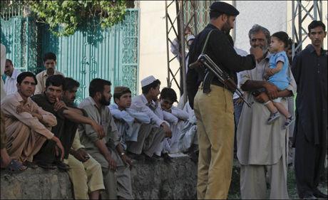 LOKALBEFOLKNING: Dette bildet av en pakistansk soldat og flere lokale innbyggere er tatt i nærheten av huset hvor Osama bin Laden gjemte seg. Foto: AP