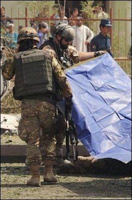 HURT LOCKER: Jørg Lian dekker til liket av en italiensk soldat, som sammen med fem kolleger ble drept av en veibombe ved Kabul i 2009. Foto: Forsvaret