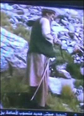 SER SEG SELV: Osama bin Laden er den som styrer fjernkontrollen hvor han ser seg selv på TV. Her med en stokk langs beina og et våpen som han nettopp har tatt opp fra bakken. Foto: Grab fra Osama-video