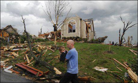 REDDET: En mann hjelper en liten gutt som ble reddet ut fra et knust hus i Joplin søndag. Foto: Ap