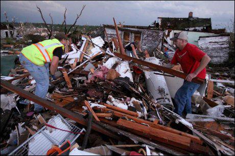 STORE ØDELEGGELSER: Frivillige redningsmannskaper fra brannvesenet leter etter en gravid kvinne som var fryktet fanget i restene av hjemmet sitt i Joplin. Foto: AP