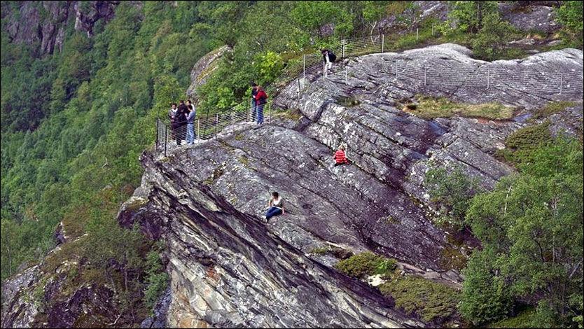PÅ KANTEN: Helt på kanten av fjellsiden sitter en kvinnelig turist langt utenfor de oppsatte sperringene. Et barn i det samme følget sitter lenger oppe, også utenfor sperringene. Foto: Ole-Petter Smørsgård