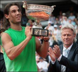 TO LEGENDER: Rafael Nadal (t.v.) tar imot French Open-trofeet i 2008 med Björn Borg i bakgrunnen. Nå står de begge med seks titler hver. Foto: AFP