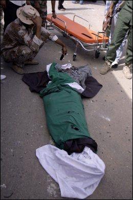 DREPT: En soldat sørger over en kamerat drapert i det libyske flagget som skal ha blitt drept under bombingen. Foto: AFP