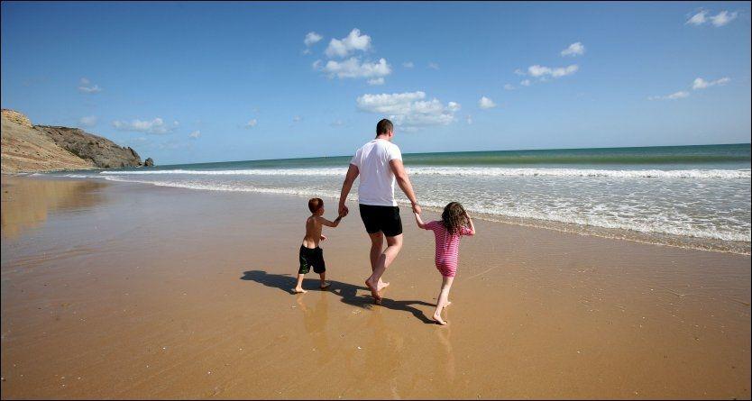 STRANDLIV: En mann leker med to barn på stranden Praia de Luz nær Lagos på Algarve-kysten i Portugal. Foto: CAMERA PRESS