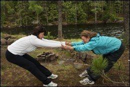 PARTNERYOGA: Susanne Hannestad og yogalærer Elizabeth Lyseng gjør partneryoga, og får en god strekk i hele kroppen. - Det er deilig å gjøre yoga utendørs, i frisk luft og med vind i håret, sier Susanne, som er på yogaferie i Nordmarka. Foto: ANNE BERGSENG.