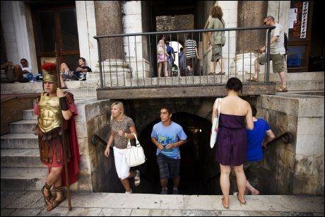LEIESOLDAT: Lovel (21) poserer villig for fotografene - hvis de betaler. Bak ham kommer folk inn fra Diokletians kjeller. Foto: TERJE BRINGEDAL / VG