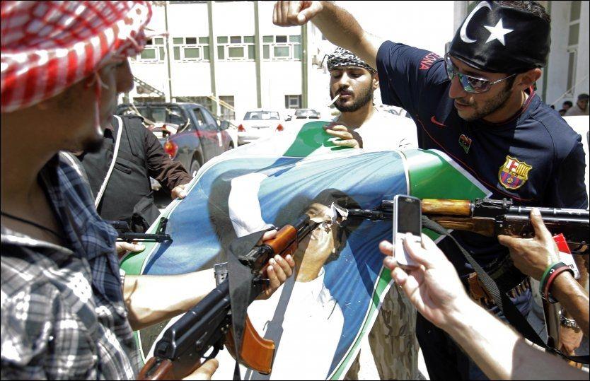 SLUTTEN?: Et portrett av Libyas diktator Moammar Gadhafi blir ødelagt av opprørere i Tripoli i dag. Foto: Ap