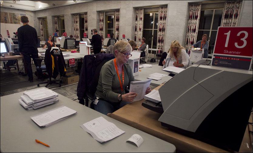 TELLER STEMMER: Aud Vestlund fra Nannestad skanner og teller stemmer i Oslo Rådhus natt til tirsdag. Hun er en av 2500 personer som jobber med stemmetelling i Oslo. Foto: Scanpix