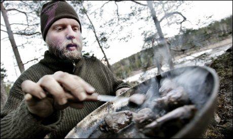 I NOVEMEBR 2009: Kristoffer Clausen steker hjortekjøtt mens han har besøk av VG i villmarken. Foto: Øyvind Nordahl Næss