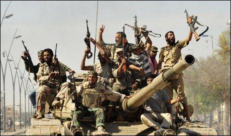 FEIRER I GATENE: Opprørere feiret i gatene i Gaddafis fødeby Sirte torsdag. Torsdag ettermiddag melder flere medier at Gaddafi skal være tatt til fange og være kritisk skadet. Foto: Reuters