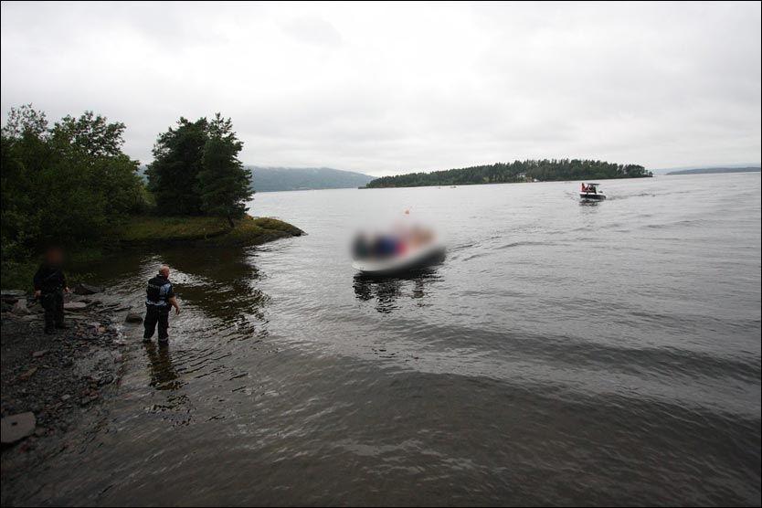 KOMMER INN MED BÅTER: Anders Behring Breivik reiste til Utvika i begynnelsen av juli for å sjekke hvordan han skulle gjennomføre massedrapene på Utøya. Her tar en politimann imot noen av Utøya-ofrene som kommer i båter inn til Utvika 22. juli. Foto: Svein Gustav Wilhelmsen