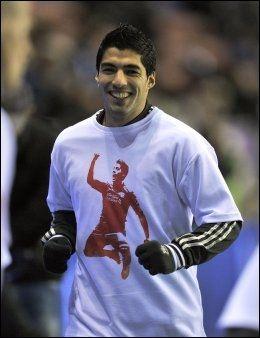 DISKUSJON Kasper Wikestad tror diskusjonen rundt Suarez kommer til å fortsette, også i julen. Her er Suarez avildet med en t-skjorte med bilde av seg selv på før kampen mot Wigan. Foto: Martin Rickett