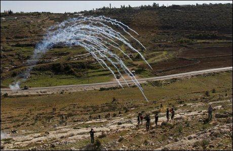 TÅREGASS: Israelske sikkerhetsstyrrker sender tåregassgranater mot palestinske demonstranter som kaster stein mot en jødisk bosetting på Vestbredden. Foto: REUTERS