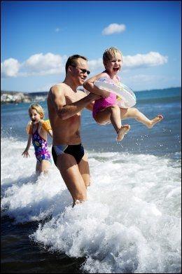 GRAN CANARIA: På denne tiden av året er det mest solsikkert på sydsiden av øya, som her på Maspalomas-stranden. Emilia Anttila (7), far Timo og Eevi (4) koser seg i bølgene. Foto: GØRAN BOHLIN