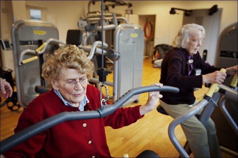 SPREKE DAMER: 90 år gamle Kiersten Torp Steinnes (t.v.) og 94 år gamle Aud Hynnekleiv er kanskje ikke de helt typiske brukerne av styrkeapparater og treningsstudio, men de løfter vekter som bare det. Flere eldre burde trene styrke, mener eksperter. Foto: Jørgen Braastad