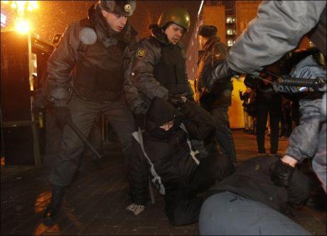 KASTET INN: Flere personer skal være kastet inn i biler etter demonstrasjonen i Moskva. Foto: Reuters