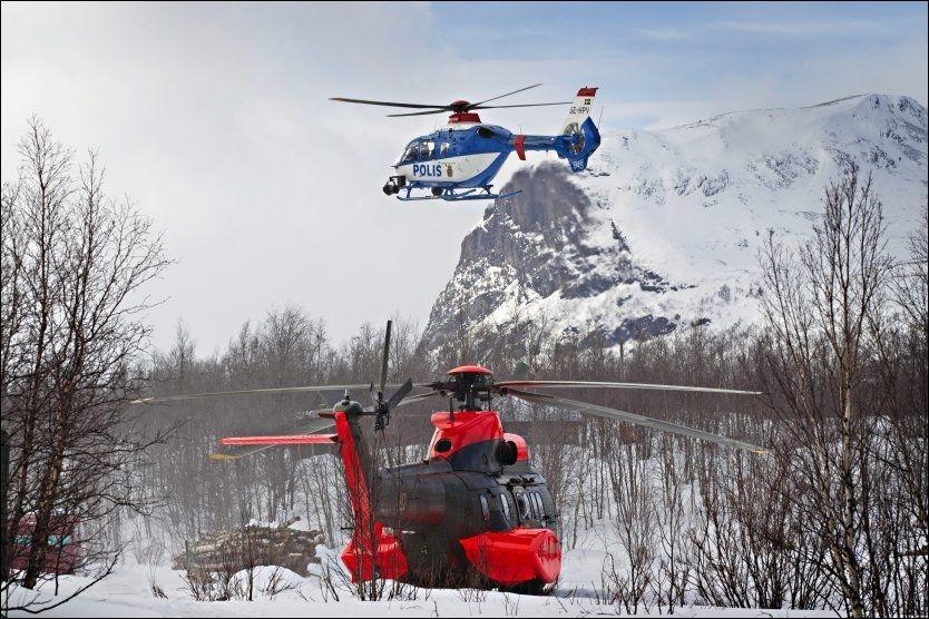LETER: To redningshelikoptre flyr inn i området. Bak dette fjellet ligger Kebnekaise hvor det lørdag ble gjort funn vrakdeler etter Hercules-flyet. Foto:Mattis Sandblad/VG
