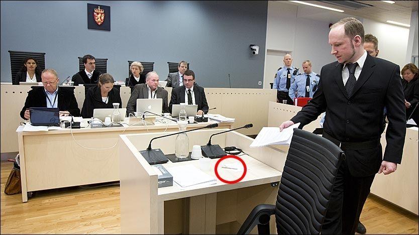 SPESIALPENN: Her tar terroristen Anders Behring Breivik (33) plass i vitneboksen torsdag formiddag. Der ligger spesialpennen han bruker. Vannkaraffelen i vitneboksen er av plast. Foto: NTB Scanpix / Heiko Junge