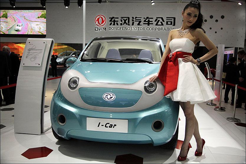 MODELLER: En bilmodell og en annen modell på årets bilutstilling i Beijing. Bilen er en elektrisk konseptbil fra Dongfeng Motor Corp. Foto: AP/Ng Han Guan